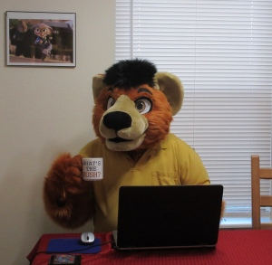 "Person in a bear costume sitting at a dinner table behind a laptop. He is wearing a yellow polo shirt and holding a coffee mug with the words ""What's the Rush?"" on it."